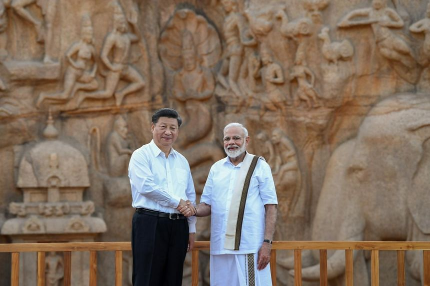 Prime Minister Narendra Modi (right) and Chinese President Xi Jinping shake hands during their visit to the Shore temple in Mamallapuram on the outskirts of Chennai, India, on Oct 11, 2019.
