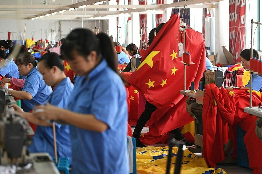 Workers making Chinese flags at a factory last month, ahead of the 70th anniversary of the founding of the People's Republic of China on Oct 1. The writer says economic growth in the country has slowed in recent quarters, raising the spectre of a lon