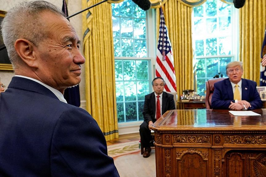US President Donald Trump spoke to reporters in his Oval Office with Chinese Vice-Premier Liu He (in the foreground) present. Mr Trump said an accord could take four to five weeks to be drafted and could be signed next month. PHOTO: REUTERS