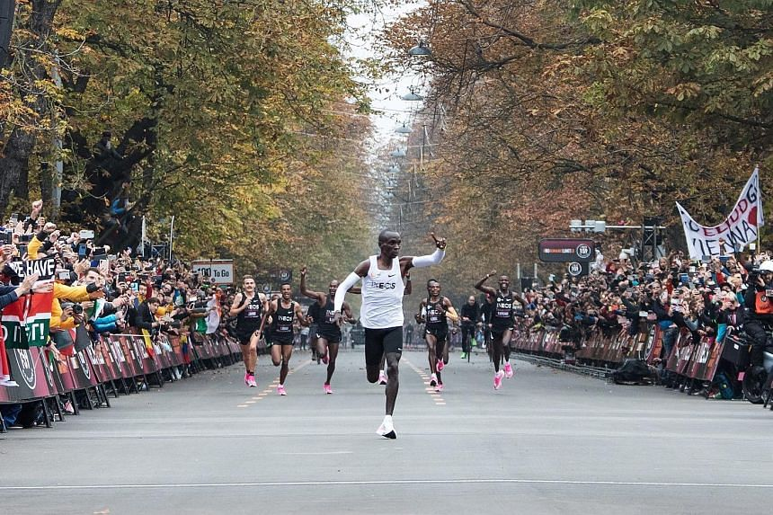 Kenya's Eliud Kipchoge waving to the crowd as he celebrates busting the mythical two-hour barrier for the marathon in Vienna yesterday - a feat that Kipchoge himself likened to a superhuman experience. PHOTO: AGENCE FRANCE-PRESSE