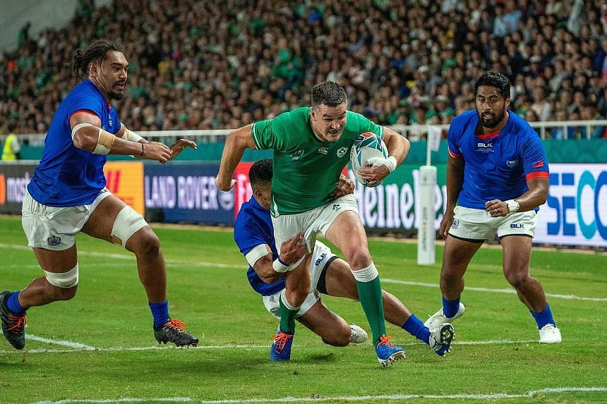 Fly-half Johnny Sexton on his way to scoring one of his two tries which gave Ireland the bonus point in the 47-5 win over Samoa in their Pool A Rugby World Cup clash in Fukuoka yesterday. PHOTO: EPA-EFE