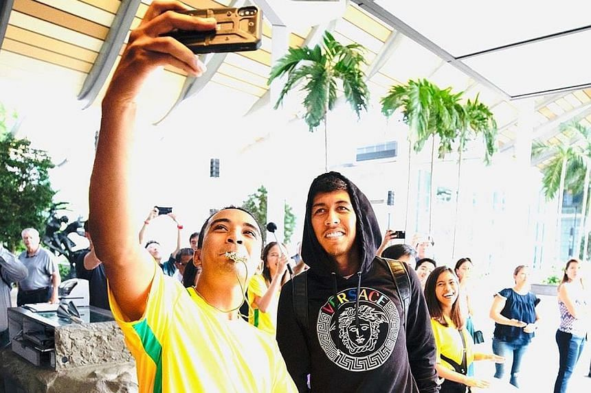 """HOT SHOT #1 """"Singapore samba"""" Local percussionist Ahmad Saifullah caught the attention of Liverpool's Roberto Firmino, and a shot with the Brazilian, after his group's loud welcome for the football team. SWEET TWEET """"Guess Who? Colleen Rooney edition"""