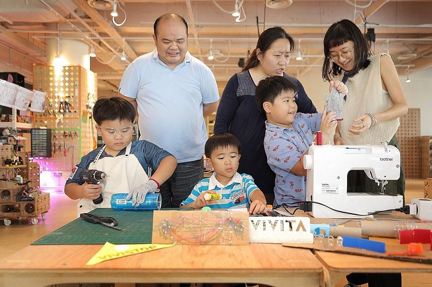 Mr Robert Sim and Ms Carol Lim let their son Ian (left, with his brothers Egan and Eli) keep up with his creative projects at VIVISTOP during exam time. Staff member Therese Heng (right) is teaching Eli how to sew.
