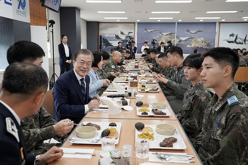 South Korean President Moon Jae-in having lunch with soldiers earlier this month at an air base in Daegu, after attending a ceremony to mark the country's 71st Armed Forces Day. Mr Moon's administration has improved the welfare of national service conscri