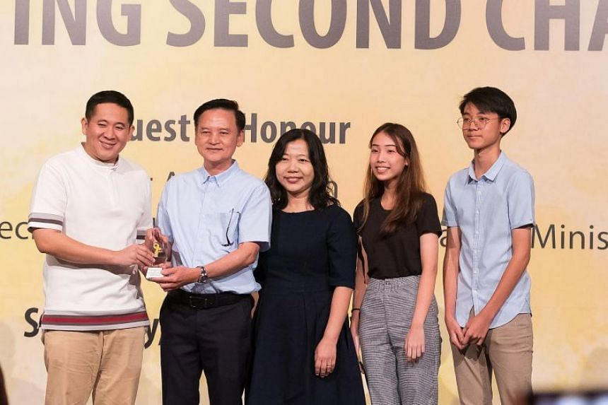 Senior Parliamentary Secretary of Home Affairs and Health Amrin Amin presenting an award to Mr Kelvin Quak (flanked by his family) at the Yellow Ribbon Celebrating Second Chances Awards Ceremony on Oct 12, 2019.