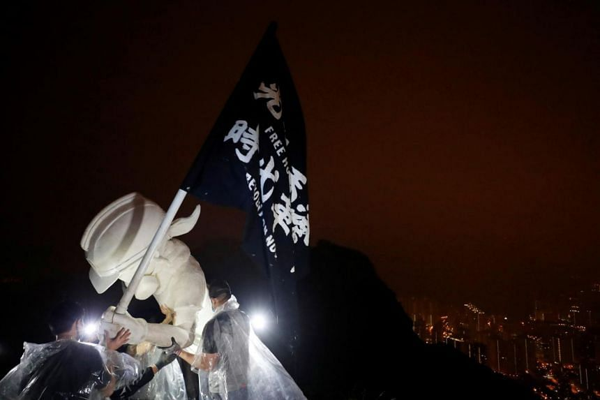 """The statue held a black banner that read """"Revolution of our time, Liberate Hong Kong"""" and could be seen from the city below."""