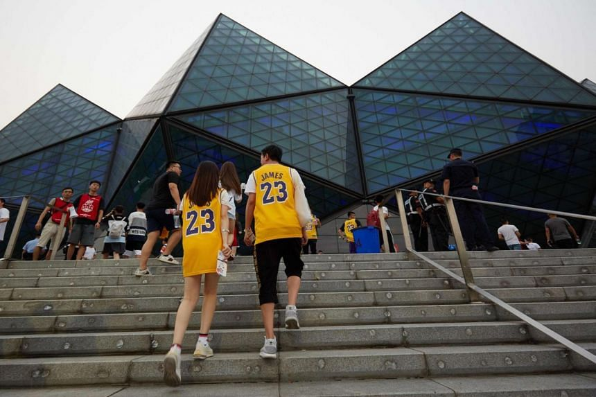 Fans wearing LeBron James shirts arrive to watch the National Basketball Association (NBA) pre-season game between the Los Angeles Lakers and Brooklyn Nets in Shenzhen, in China's southern Guangdong province on Oct 12, 2019.
