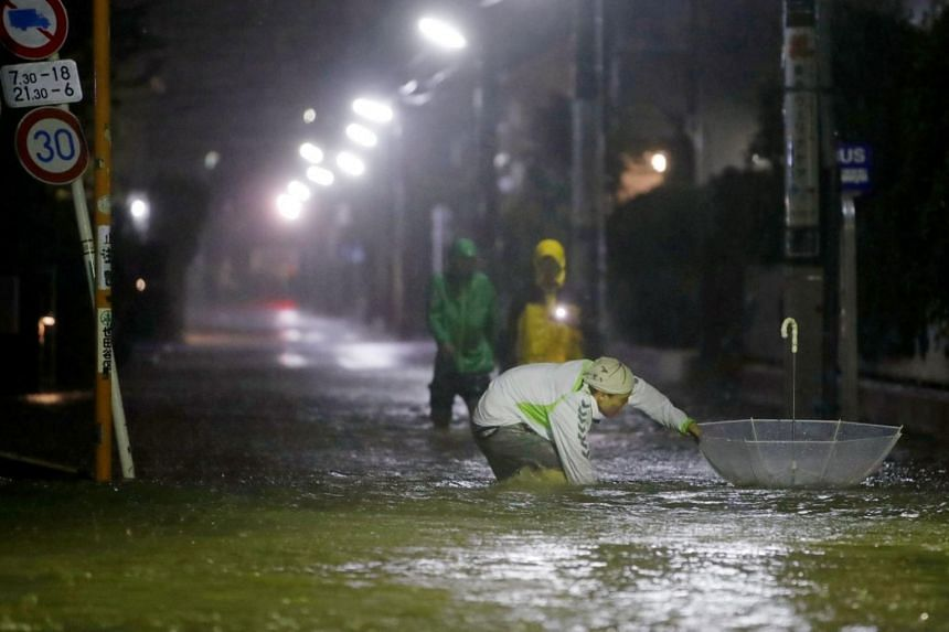 A man tries to retrieve an umbrella in roads flooded due to heavy rains caused by Typhoon Hagibis at Setagaya ward in Tokyo, Japan on Oct 12, 2019.