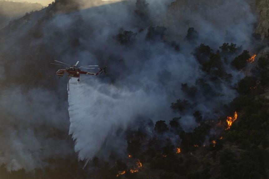 A firefighting helicopter drops water on the Saddleridge Fire on Oct 11, 2019 near Newhall, California.