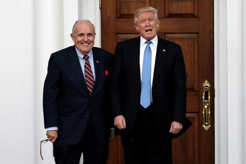 In a file photo taken on Nov 20, 2016, US President Donald Trump stands with former New York City Mayor Rudolph Giuliani before their meeting at Trump National Golf Club in Bedminster, New Jersey.