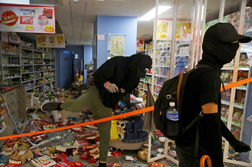 Protesters leave a vandalised store in New Town Plaza on Oct 13, 2019.