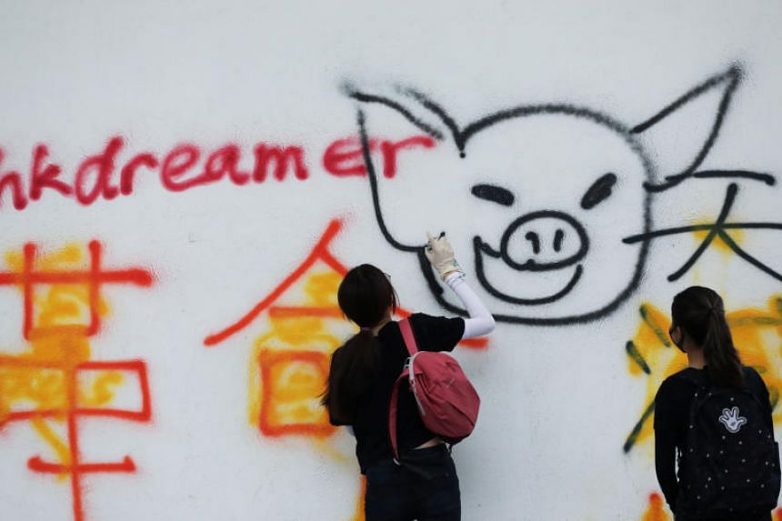 A protester sprays graffiti onto a wall in Hong Kong's Wong Tai Sin district on Oct 13, 2019.