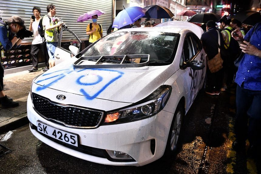 Protesters trash what they suspect to be an unmarked police car in Mong Kok, Hong Kong, on Oct 13, 2019.