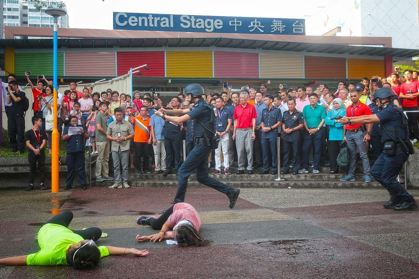 Police officers reacted to a simulated attack by a gunman in Ang Mo Kio yesterday as Prime Minister Lee Hsien Loong, who is an MP for Ang Mo Kio GRC, watched intently along with many other people. Held at Ang Mo Kio Central Stage, the live exercise b