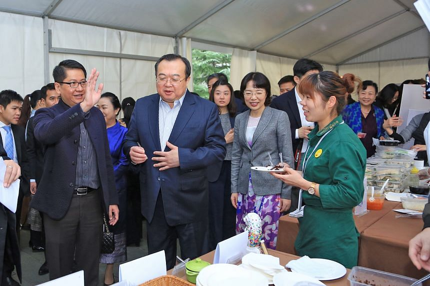 Singapore Ambassador to China Stanley Loh (in striped shirt) accompanying Deputy Director of the Central Foreign Affairs Commission Office Liu Jianchao and Chongqing Vice-Mayor Pan Yiqin (in grey jacket) at the charity bazaar held at the Singapore Em