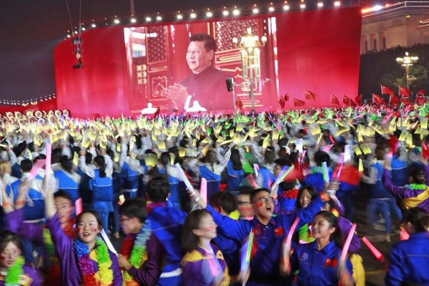 Performers in a pageant in front of a screen showing Chinese President Xi Jinping, during celebrations on Oct 1 marking the 70th anniversary of the founding of the People's Republic of China.
