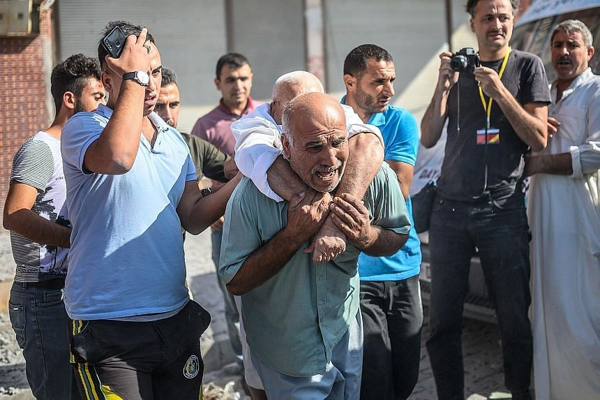 An elderly man being evacuated from a building in Akcakale, Turkey, yesterday after it was hit by a rocket reportedly fired from Syria.