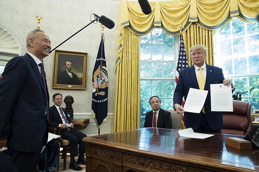 US President Donald Trump with a letter from Chinese President Xi Jinping, presented by China's top trade negotiator Liu He (left), in Washington on Friday. The US and China agreed to the first phase of a deal to end the trade war, with the agreement