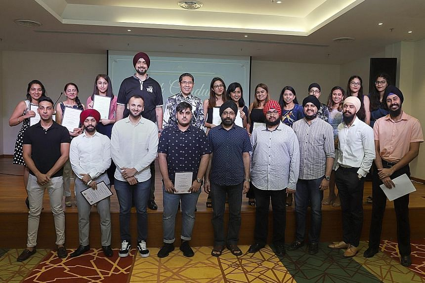Senior Minister of State for Defence and Foreign Affairs Maliki Osman (back row, centre) with Dr Ishwarpal Singh Grewal (front row, far right) and other young graduates at the annual Sikh Graduates Tea yesterday.