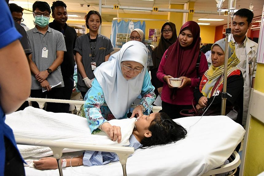 Malaysian Deputy Prime Minister Wan Azizah Wan Ismail with one of the injured at Putrajaya Hospital on Saturday. Sixteen people, including nine children, were hurt when the balloons exploded at a fitness event.