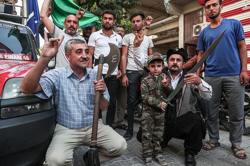 Above: Syrian rebel fighters backed by Ankara in the village of Yabisa, Syria, near the border with Turkey yesterday. Left: A group of ultra-nationalist demonstrators gathered in Akcakale, Turkey, yesterday in support of the Turkish operation against