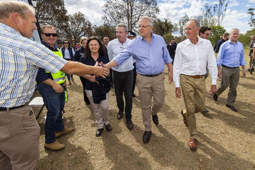 Australian Prime Minister Scott Morrison (centre) greeting members of the local community during a visit to fire-affected Rappville in New South Wales yesterday. Mr Morrison has indicated that he will side with the US in its trade war with China, but