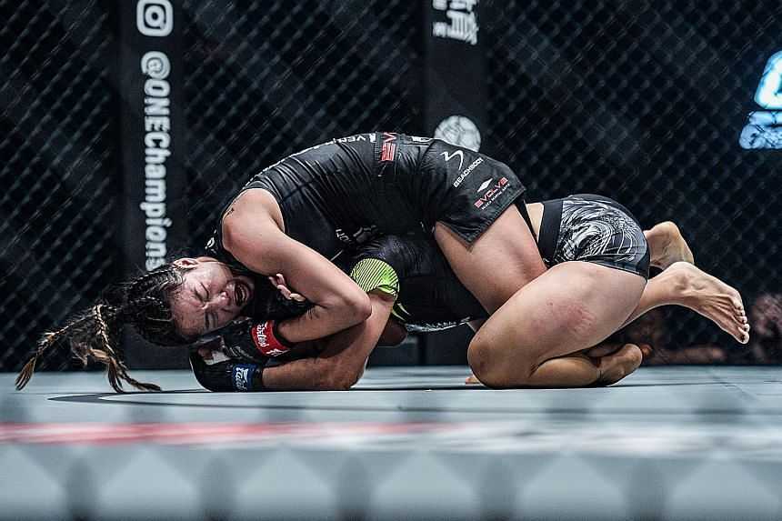 Angela Lee tightening her grip on the rear-naked choke hold on China's Xiong Jingnan in their atomweight title bout at One:Century in Tokyo yesterday. PHOTO: ONE CHAMPIONSHIP