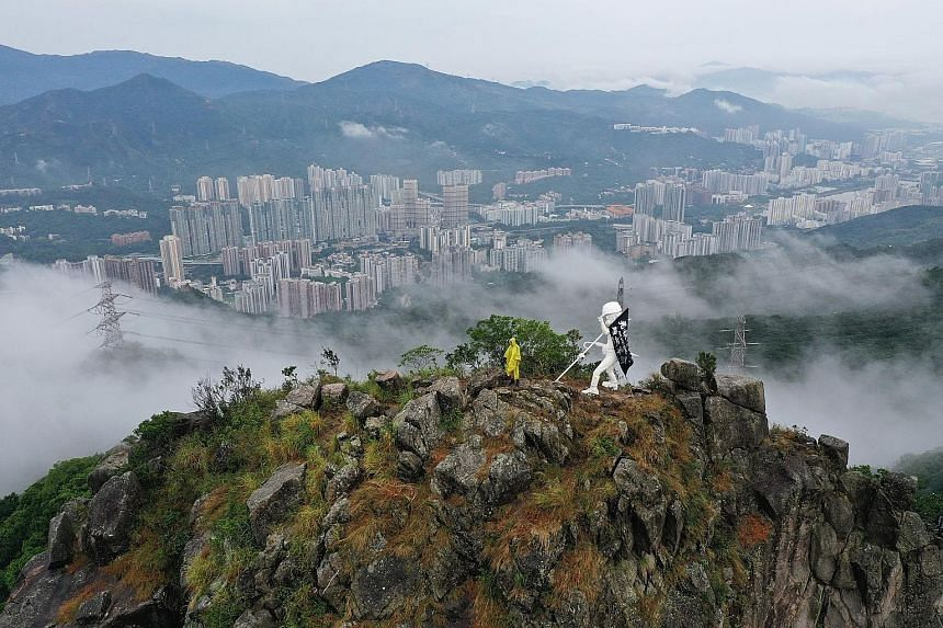 The Lady Liberty statue overlooking the city from up on Lion Rock peak in Hong Kong. The white statue of a protester with a helmet and gas mask was created so that the pro-democracy movement could have its own symbol of democracy instead of borrowing