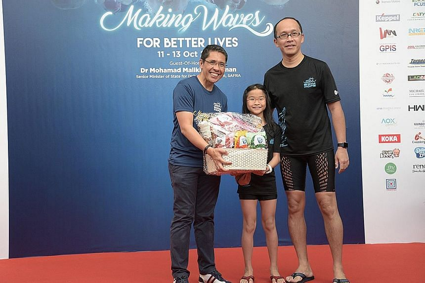 Safra president Maliki Osman presenting a hamper yesterday to Mr Ong Chin Hwee and his 10-year-old daughter Wen Yi, who finished as runners-up in the Families for Life category of the Safra Swim for Hope event.