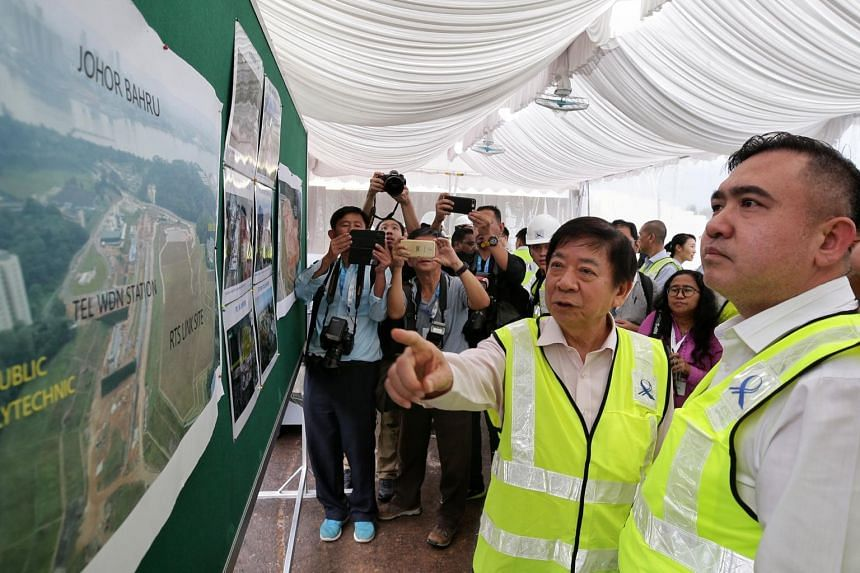 In a photo taken on May 21, 2019, Transport Minister Khaw Boon Wan (left) and his Malaysian counterpart Anthony Loke is seen looking at an aerial shot of the Rapid Transit System Link site in Woodlands North.