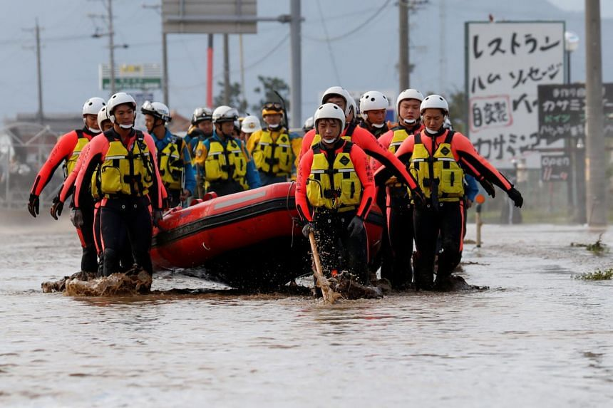Rescue workers carry a rubber dinghy as they search a flooded area in the aftermath of Typhoon Hagibis in Nagano Prefecture, Japan, Oct 14, 2019.