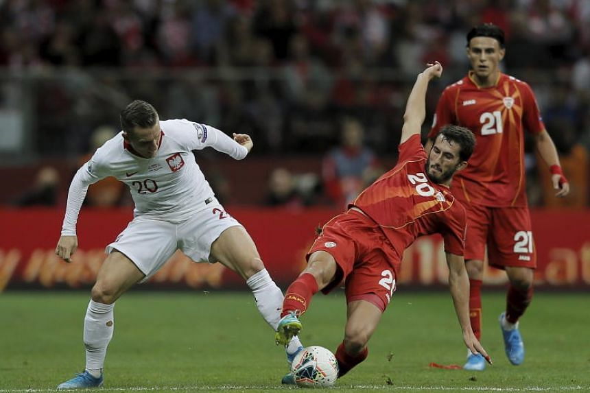 Poland's Piotr Zielinski (left) and Stefan Spirovski (right) and North Macedonia in action during the Uefa Euro 2020 group G qualifying soccer match between Poland and North Macedonia at PGE National stadium in Warsaw, Poland, on Oct 13, 2019.