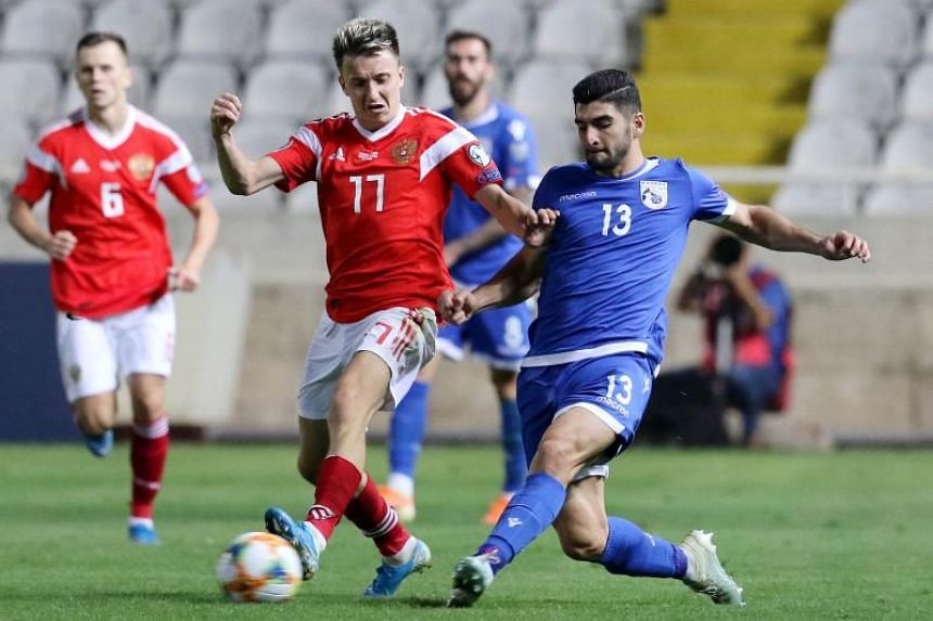 Cyprus' defender Ioannis Kousoulos (right) vies for the ball with Russia's midfielder Aleksandr Golovin (centre) during the Euro 2020 group I qualifiers football match between Cyprus and Russia at the GSP stadium in the capital Nicosia, on Oct 13, 20