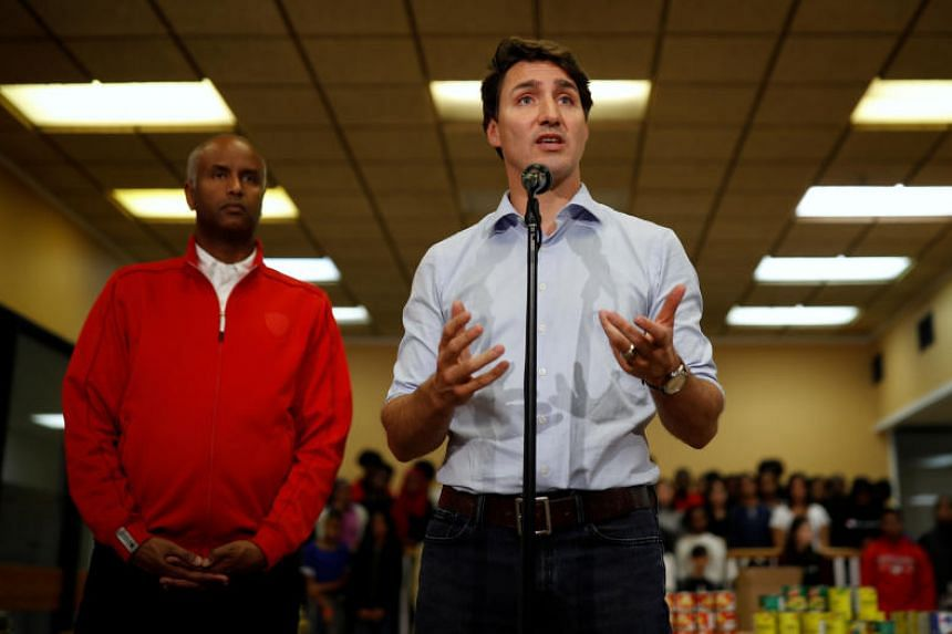 Canadian Prime Minister Justin Trudeau speaks next to Liberal candidate for York South-Weston, Ahmed Hussen, during a Thanksgiving food drive in Toronto, Ontario, Canada, on Oct 13, 2019.