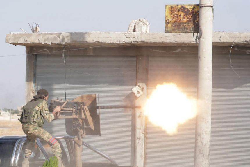 A Turkey-backed Syrian rebel fighter fires a weapon in the town of Tal Abyad, Syria, on Oct 13, 2019.