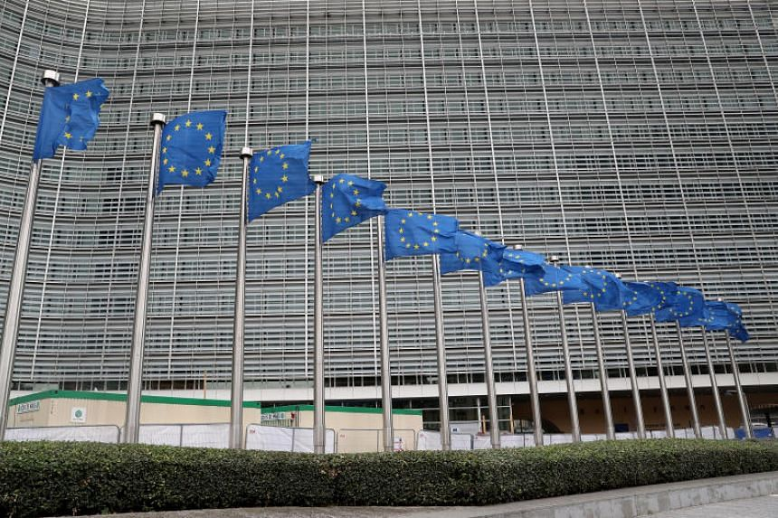 A photo taken on Oct 4 shows European Union flags outside the European Commission headquarters in Brussels. EU governments have agreed to limit arms exports to Turkey over its offensive in northern Syria.