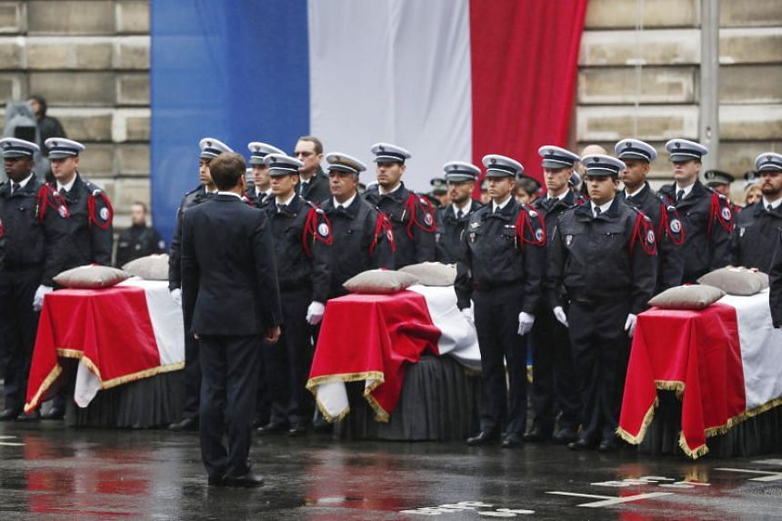 A photo taken on Oct 8 shows French President Emmanuel Macron paying tribute to the victims of the Oct 3 knife attack at the headquarters of the Paris police, during a ceremony in Paris.