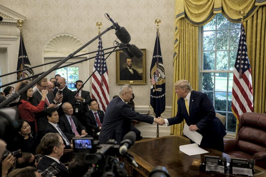 A photo taken on Oct 11 shows US President Donald Trump with Chinese Vice-Premier Liu He in the Oval Office of the White House in Washington.