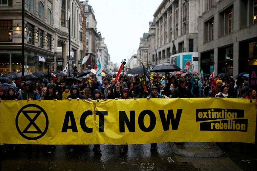 In a photo taken on Oct 12, climate change activists attend an Extinction Rebellion demonstration in London.