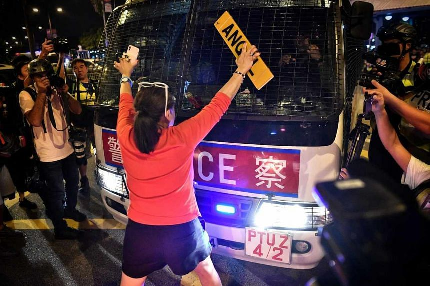 A woman tries to stop a police van from leaving the Central Ferry Pier on Oct 14, 2019.