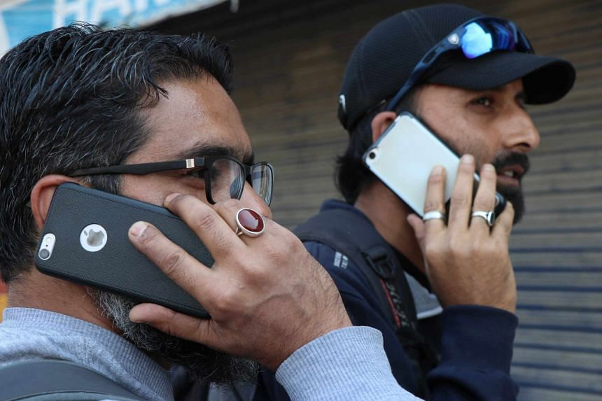 Kashmiri youth busy with mobile phones after government authorities lift ban on postpaid mobile phones in Kashmir valley, in Srinagar on Oct 14, 2019.