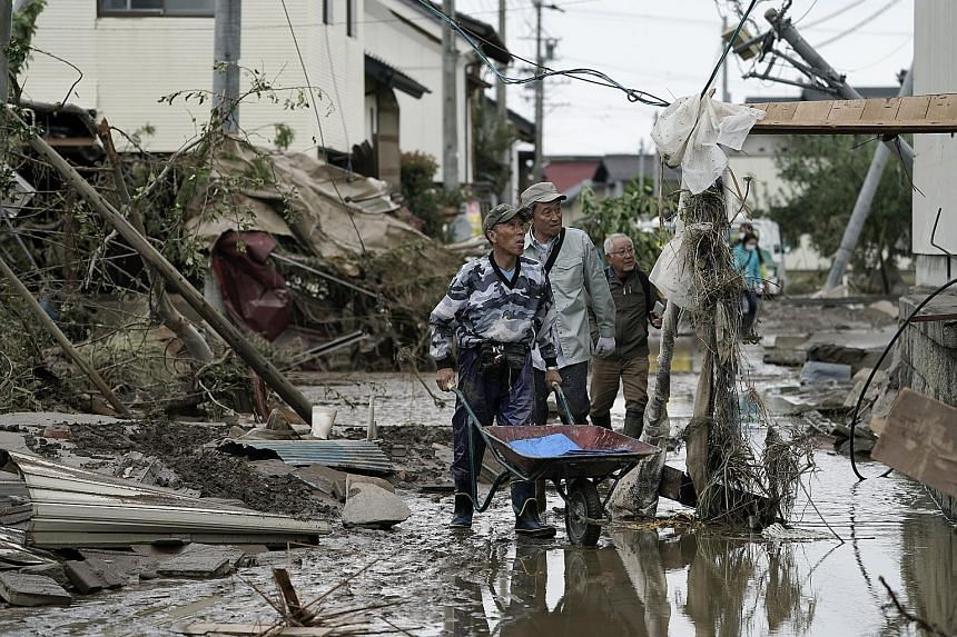 Residents walking through a typhoon-affected area in the aftermath of Typhoon Hagibis in Nagano, Japan, yesterday. PHOTO: EPA-EFE