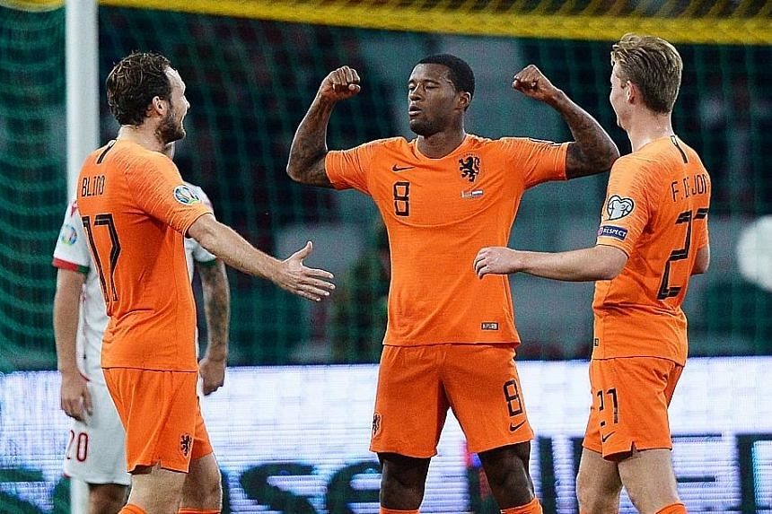 Gini Wijnaldum (No. 8) celebrating his second goal, a spectacular long-range strike, against Belarus with Daley Blind and Frenkie de Jong. PHOTO: EPA-EFE