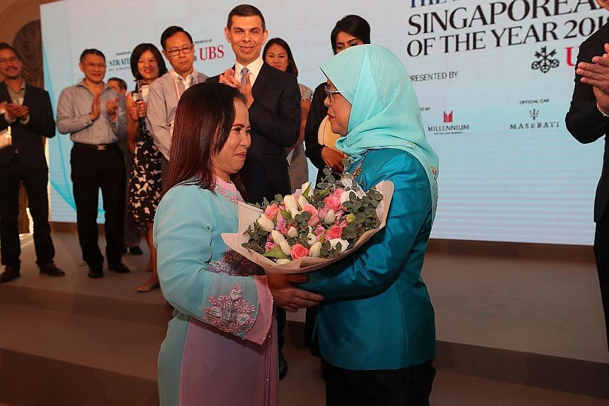 A file photo of Madam Noriza A. Mansor giving a bouquet to President Halimah Yacob at The Straits Times Singaporean of the Year award ceremony in February this year. Madam Noriza, who was there as a guest, won the inaugural ST Singaporean of the Year