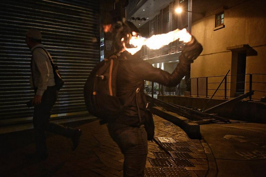 In a photo from Oct 4, 2019, a protester throws a petrol bomb to light up a fire roadblock to impede police in Wan Chai, Hong Kong.