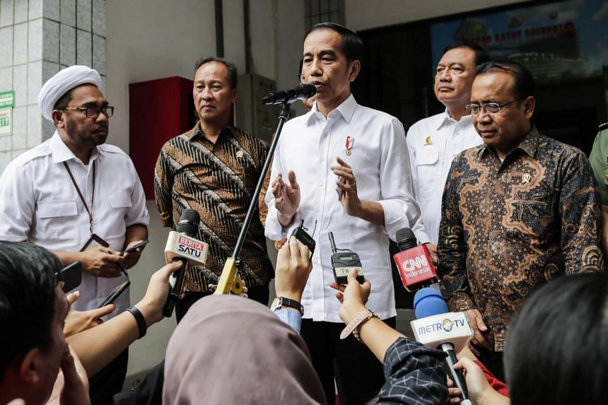 Indonesian President Joko Widodo (centre) talks to media after visiting wounded Security Minister Wiranto at the Gatot Subroto army hospital in Jakarta, on Oct 10, 2019.