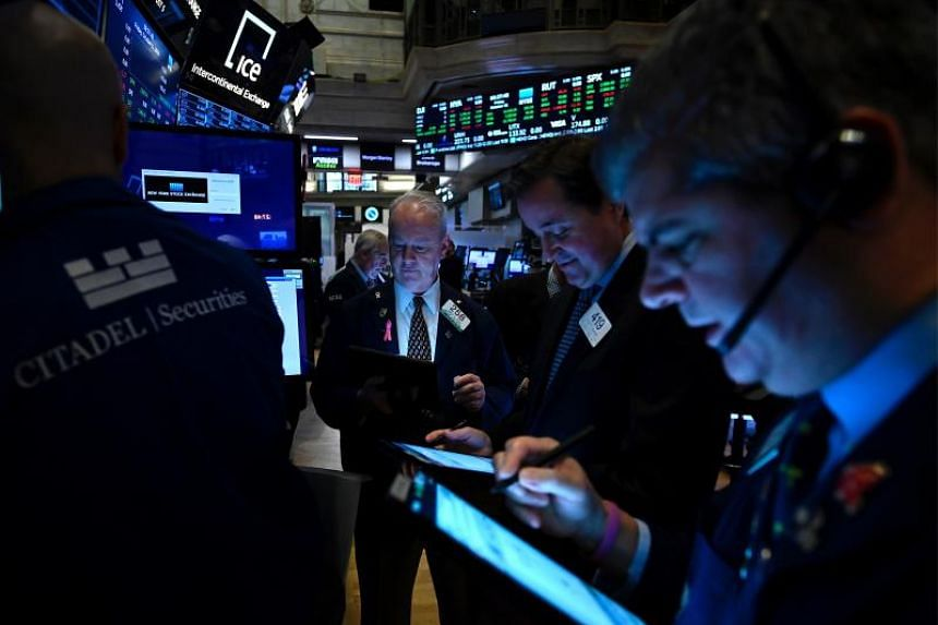 Traders work at the New York Stock Exchange (NYSE) at Wall Street in New York City.