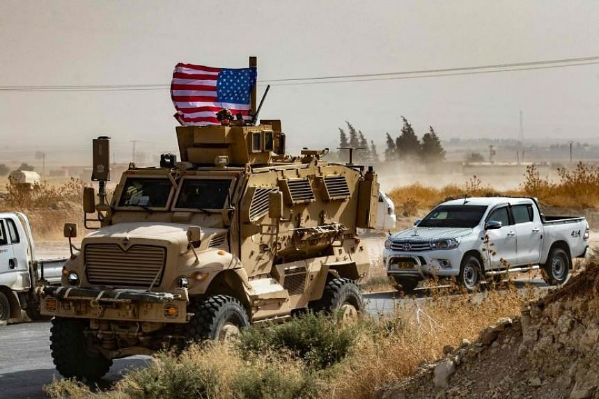 In this photo taken on Oct 6, 2019, a US soldier sits atop an armoured vehicle during a demonstration by Syrian Kurds against Turkish threats next to a base for the US-led international coalition on the outskirts of Ras al-Ain town in Syria's Hasakeh