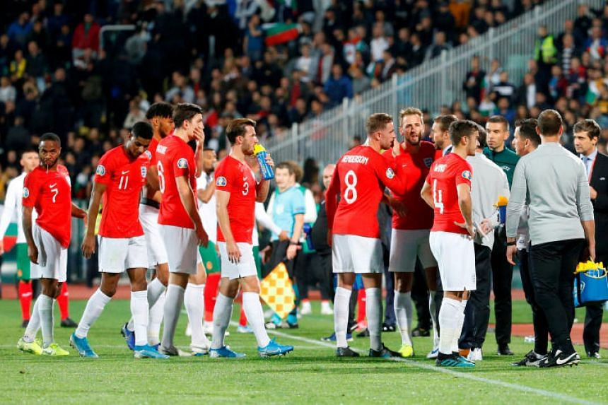 England players speak with manager Gareth Southgate as the Euro 2020 Group A match against Bulgaria is temporarily stopped during the first half.