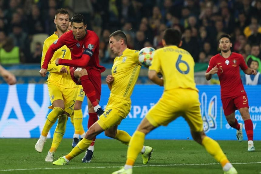 Ukraine's Serhiy Kryvtsov (centre) in action against Portugal`s Cristiano Ronaldo (second left) during the UEFA Euro 2020 qualifying round, Group B soccer match Ukraine vs Portugal at Olympic stadium, in Kiev, Ukraine, on Oct 14, 2019.